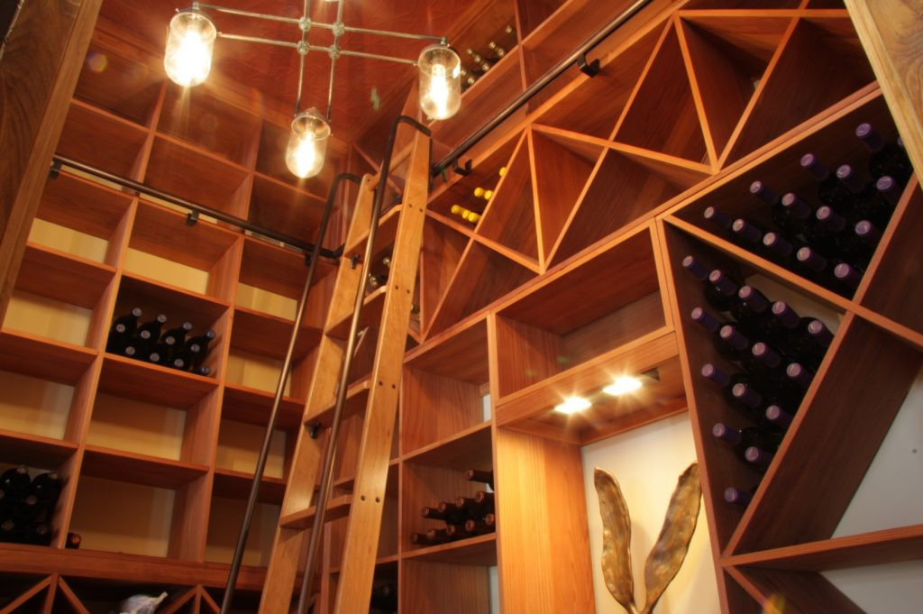 Custom wooden racking and a rolling ladder in a beautiful wine cellar
